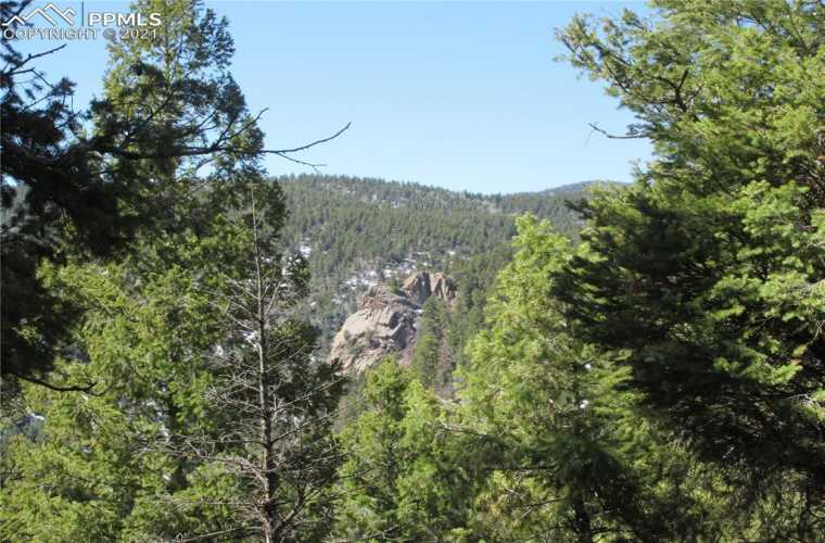 View of beautiful rock formations to the west. This beautiful 2.55-acre lot has a wonderful west-facing view ready to build your dream home in the mountains in the highly sought-after gated community of Woodmoor Mountain.
